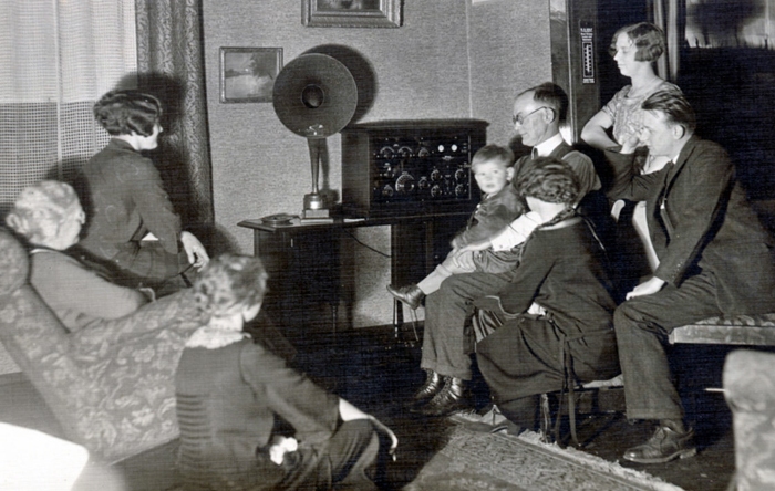 A family gathers around to listen to Cladrite Radio