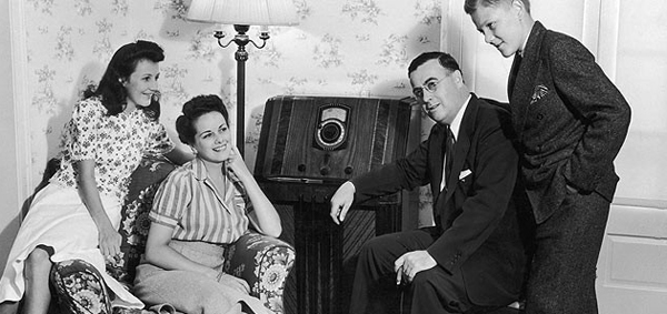 A family in the 1930s listens intentlyl to a large radio.